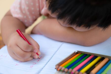 Close up of girl hand with pencil writing english words by hand on  white notepad paper at white background, Child learning to write letters of the alphabet, A child is holding a crayon in his hands at paper and crayons for drawing