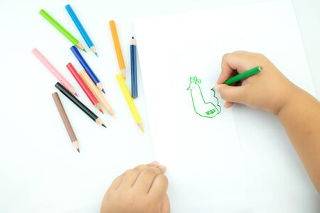 Children draw paints in the playroom, A child is holding a crayon in his hands at paper and crayons for drawing on the table, Hand Kids drawings,  childrens creativity 版權商用圖片