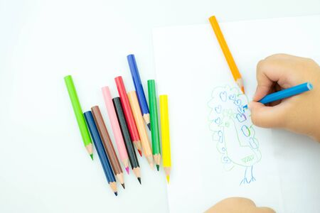Children draw paints in the playroom, A child is holding a crayon in his hands at paper and crayons for drawing on the table, Hand Kids drawings,  childrens creativity Фото со стока