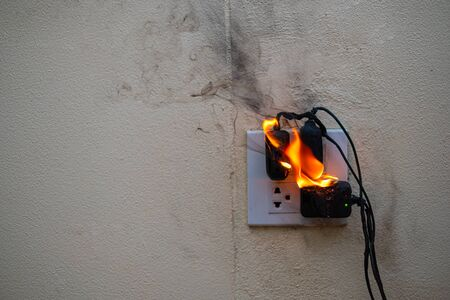 On fire adapter at plug Receptacle on white background, Electric short circuit failure resulting in electricity wire burnt Banco de Imagens