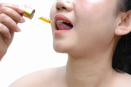 Woman holding a dropper sublingual Cannabis oil at white background