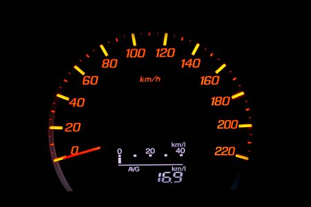 Close up of car speedometer with the needle pointing at kmp on black blackground