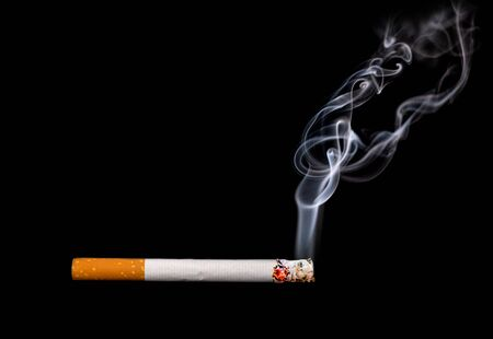 Close up of a cigarette with smoke showing at black background Stok Fotoğraf
