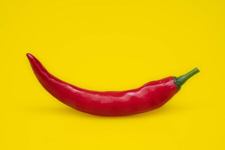 Close up red Hot chili spur pepper at yellow background