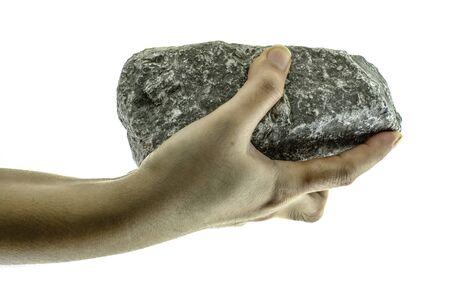 La mano ravvicinata tiene in mano una pietra isolata su sfondo bianco Archivio Fotografico