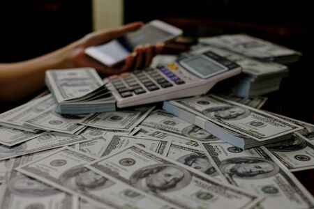 Hand holding smartphone and calculator on a stack of 100 US dollars banknotes lots of money