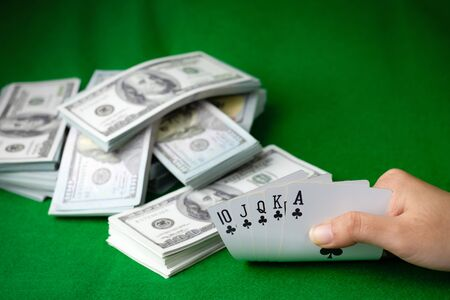 Poker casino gambling Royal Straight Flush and the money stack of 100 US dollars banknotes at the green background, Hand holding Playing card club 5 cards Stok Fotoğraf