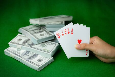 Poker casino gambling Royal Straight Flush and the money stack of 100 US dollars banknotes at the green background, Hand holding Playing card Heart 5 cards