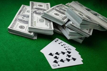 Poker casino gambling Royal Straight Flush and the money stack of 100 US dollars banknotes at the green background, Playing card club 5 cards