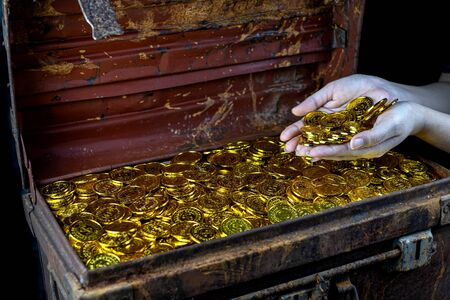 Lots of stacking Gold Coin in lady hand and treasure chest at black background