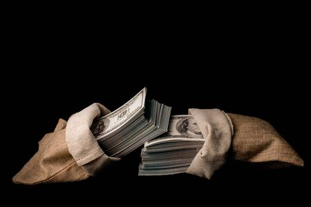 Sack of money 100 USD dollars banknotes a lot of money at black background Archivio Fotografico