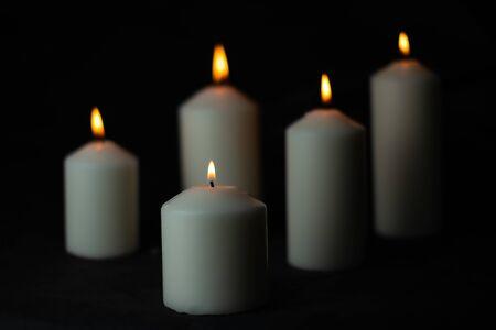 Vijf lichte vlamkaars die fel branden op zwarte achtergrond