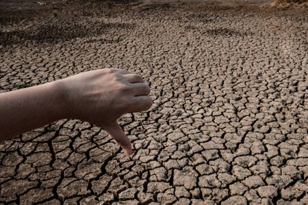 Women hand thumbs down on cracked and dry soil in arid areas landscape, Drought crisis Concept Stockfoto