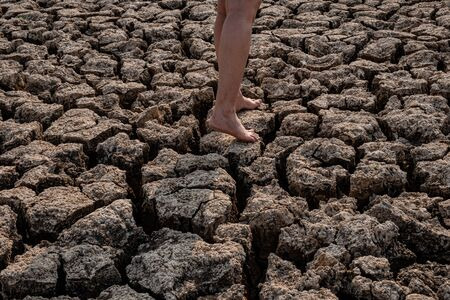 Women walking on cracked and dry soil in arid areas landscape, Drought crisis Concept Stockfoto