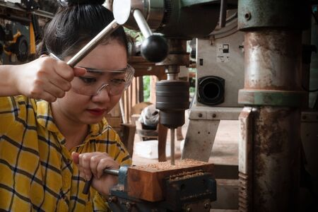 Women standing is craft working drill wood at a workbench with Drill Press power tools at carpenter machine in the workshop 스톡 콘텐츠