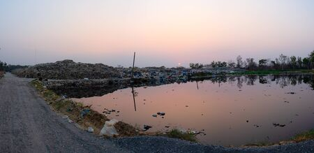 Polluted water and mountain large garbage pile and pollution at the sun is setting in the background panorama, Pile of stink and toxic residue, These waste come from urban and industrial areas can not get rid of 스톡 콘텐츠