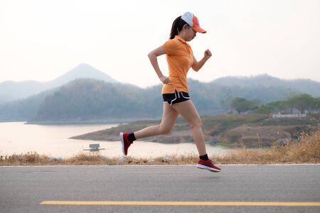 Photo side view Asia young woman runner running on asphalt road, female in sport cloth jogging at the park, Healthy lifestyle concept