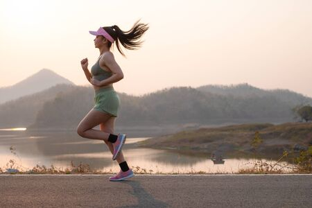 Photo side view Asia young woman runner running on asphalt road at riverside, female in sport cloth jogging at the park, Healthy lifestyle concept