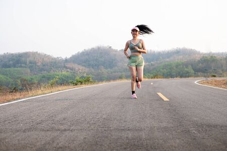 Photo fone view Asia young smiling woman runner running on asphalt road, female in sport cloth and wear a hat jogging, Healthy lifestyle concept