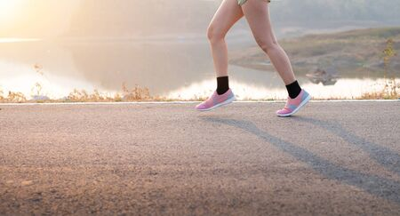 Photo front view Sporty Asian young woman wear sports shoes running on asphalt road, Fitness and workout wellness, Healthy lifestyle concept