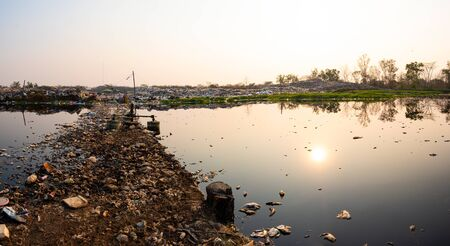 Polluted water and mountain large garbage pile and pollution at the sun is setting in the background, Pile of stink and toxic residue, These waste come from urban and industrial areas can not get rid of