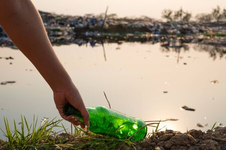 Hand-picking up  green glass bottle and bottle at mountain large garbage background, These waste come from urban and industrial areas can not get rid of, Pile of stink and toxic residue