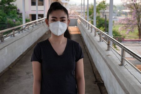 Close up of a woman standing putting on a respirator N95 mask to protect from airborne respiratory diseases as the flu covid-19 coronavirus ebola PM2.5 dust and smog on the road burred background