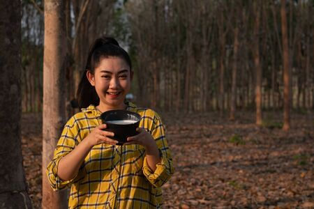 Portrait gardener young asea woman hand holding a full cup of raw para rubber milk of tree in plantation rubber tapping form Thailand, good farm produce, Hevea brasiliensis