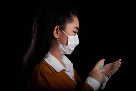 Businesswoman of young Asia woman putting on a respirator N95 mask with the hand that applying alcohol spray from the plastic bottle or anti bacteria to prevent the spread of germs at black background