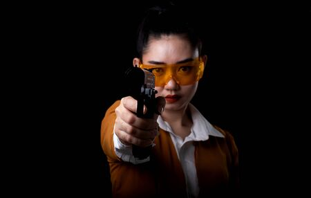 Women pointing a guns look at the camera, Portrait beautiful asea woman wearing a yellow suit one hand holding pistol gun at the black background, Young sexy girl long hair with a handgun 스톡 콘텐츠