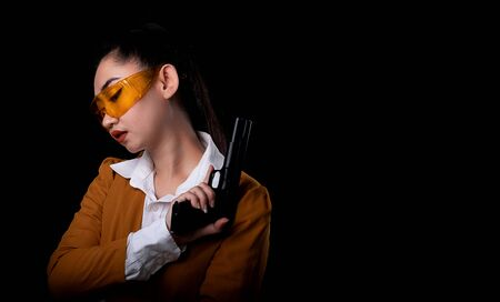 Portrait beautiful asea woman wearing a yellow suit one hand holding pistol gun at the black background, Young sexy girl long hair with a handgun lool at the camera, Pretty women stands with a guns