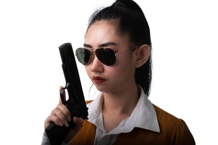 Portrait beautiful asea woman wearing a yellow suit one hand holding pistol gun at the white background, Young sexy girl long hair with a handgun look at the camera, Pretty women stand with a guns