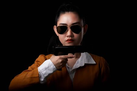 Portrait beautiful asea woman wearing a yellow suit one hand holding pistol gun at the black background, Young sexy girl long hair with a handgun look at the camera, Pretty women stand with a guns