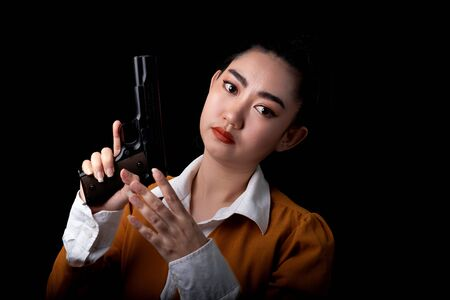 Portrait beautiful asea woman wearing a yellow suit one hand holding a pistol gun at black background, Young sexy girl long hair with a handgun look at the camera, Pretty women stands with a pistol