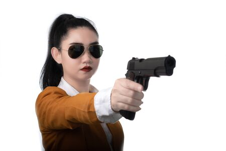 Portrait beautiful asea woman wearing a yellow suit one hand holding a pistol gun at white background, Young sexy girl long hair with a handgun look at the camera, Pretty women stands with a pistol 스톡 콘텐츠