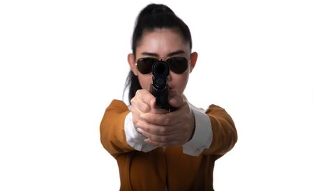Women pointing guns look at the camera, Portrait beautiful asea woman wearing a yellow suit one hand holding pistol gun at the white background, Young sexy girl long hair with a handgun 스톡 콘텐츠