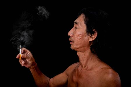 The portrait slim old man was smoking at the black background, Image of men hand holding cigarette smoke spread in the mouth concept