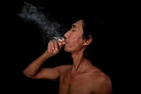 The portrait slim old man was smoking at the black background, Image of cigarette smoke spread in the mouth concept Stock Photo
