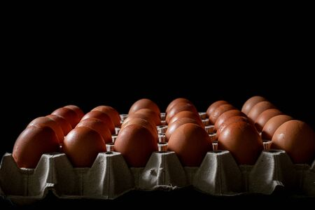 Eggs carton with chicken egg lined up in rows at black background Standard-Bild