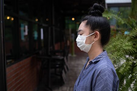 Close up of young Asia woman standing putting on a respirator N95 mask to protect from airborne respiratory diseases as the flu covid-19 coronavirus ebola PM2.5 dust and smog on the road burred background Archivio Fotografico
