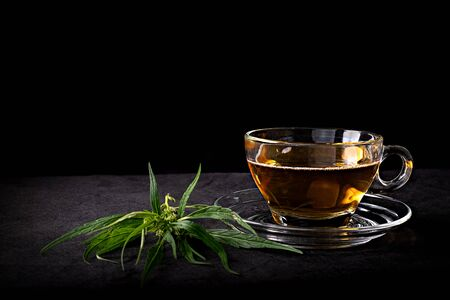 Cannabis tea in a clear glass cup with a green marijuana leaf and stem on wood table at the black background, Herbal and healthy drinks concept 版權商用圖片