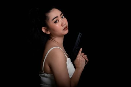 Portrait beautiful Asia woman one hand holding gun at the black background, Young sexy girl long hair with a handgun, Pretty women stand with a pistol, look at camera Banco de Imagens