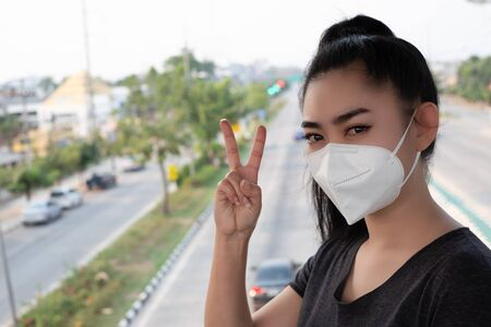 Woman standing hand sign of 2 fingers with putting on respirator N95 mask to protect from airborne respiratory diseases as the flu covid-19 coronavirus PM2.5 dust and smog on the road burred backgro
