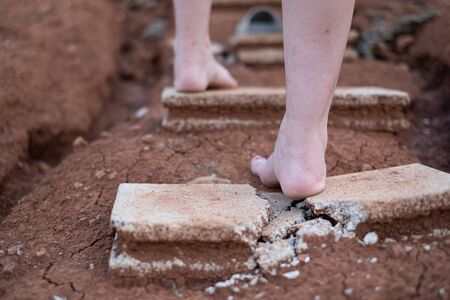 Photo close up of shards of a broken concrete block at woman barefoot at the walking