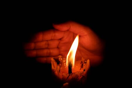 Hand protecting candle light from the wind in darkness on black background