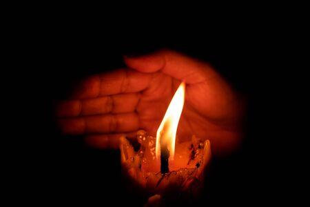 Mano che protegge la luce della candela dal vento nell'oscurità su sfondo nero