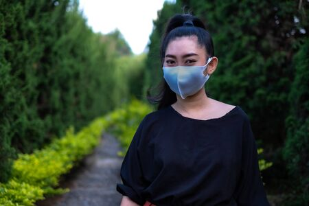 Young Asia woman standing and put on a face mask to protect from airborne respiratory diseases as the flu dust and smog in the park, Women safety virus infection concept