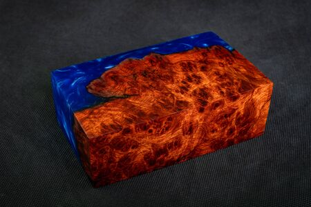 Casting blue epoxy resin with nature burl BURMA PADAUK wood cube on black background