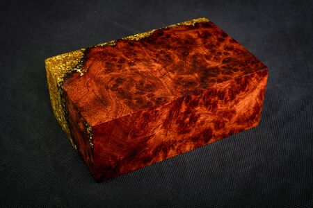 Casting epoxy resin gold with nature burl BURMA PADAUK wood cube on black background Stok Fotoğraf