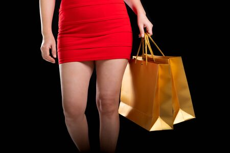 Portrait of a beautiful woman wearing a red dress holding shopping bags a black background, sale concept, front view Stock Photo